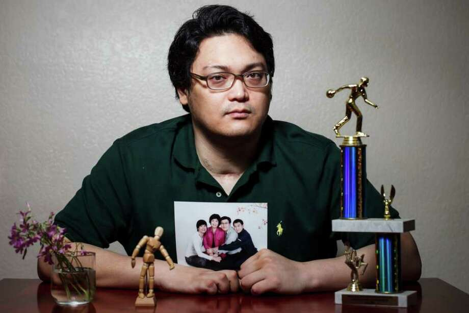 Dominic Park, a Korean student at the University of Houston who was paralyzed in a carjacking, shows off a family photo and a bowling trophy earned before the shooting. Photo: Michael Paulsen / © 2012 Houston Chronicle