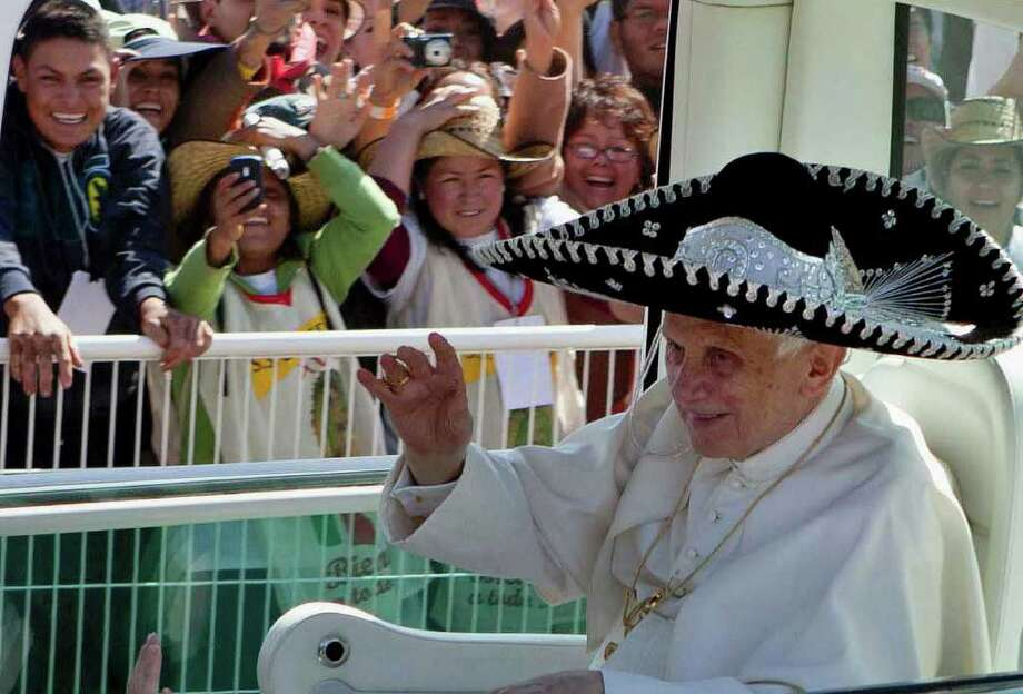 A sombrero-topped Pope Benedict XVI arrives Sunday in Silao, Mexico, in the popemobile. At an outdoor Mass before an estimated 640,000 people, Benedict urged Catholics to cling to their faith to overcome hardships. Photo: Eduardo Verdugo / AP