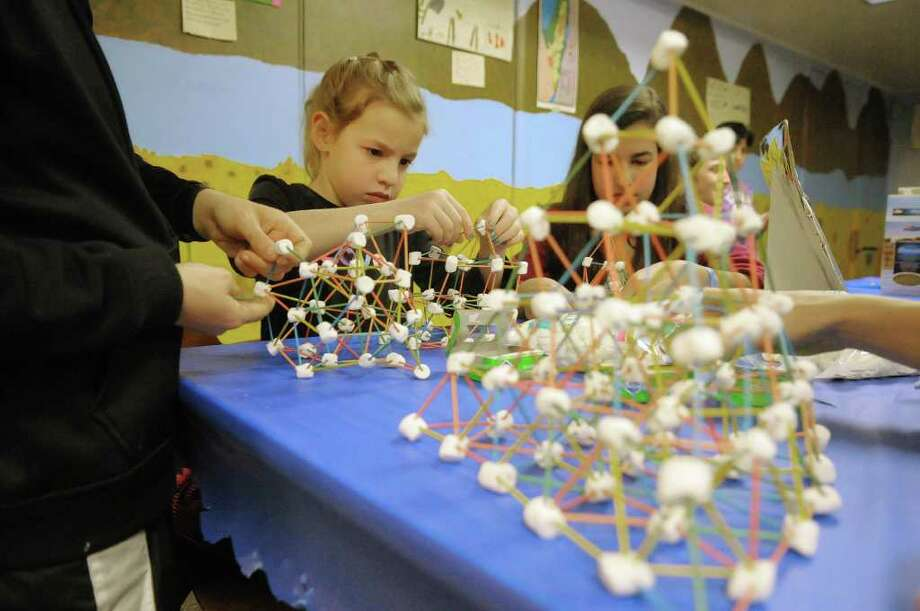 Alise Hale, left, 8, and her sister Grace Hale, right, 13, from Niskayuna, make structures out of toothpicks and marshmallows at the 9th Annual Jewish Food Festival at the Congregation Gates of Heaven on Sunday, March 25, 2012 in Schenectady, NY.  The event features Jewish culture food from regional restaurants and caterers and from individual congregants.  Organizers said that between 600 to 700 people attend the single day evet ad each year attendance grows by about 10%.  (Paul Buckowski / Times Union) Photo: Paul Buckowski