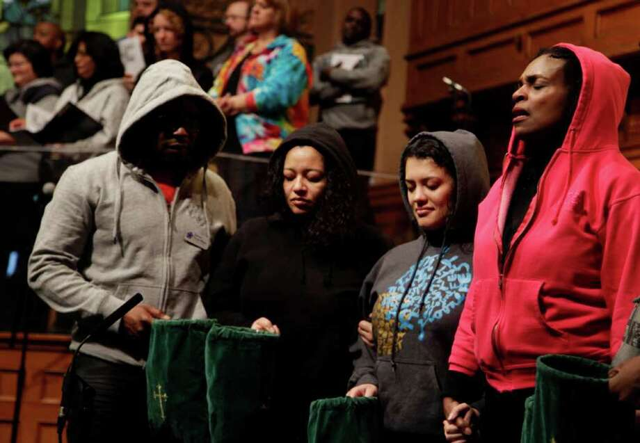 Senior Minister Jacqueline Lewis, right, prays with other congregants during a service at Middle Collegiate Church in New York, Sunday, March 25, 2012. Church-goers were invited to wear hoodies to services to show their support for justice in the case of Trayvon Martin, an unarmed black teenager who was wearing a hoodie on the night he was killed by a neighborhood watch captain in Florida. (AP Photo/Seth Wenig) Photo: Seth Wenig