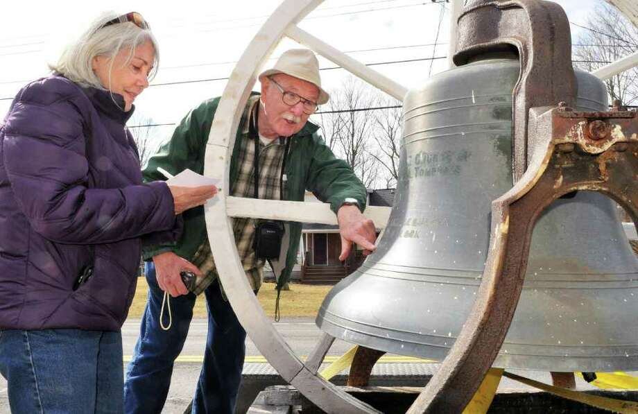 Village of East Nassau historian Linda Dellea, left, and George Herrick of East Greenbush, once a lay speaker at the church examine an 1880 Meneely bell recovered from The  Brainard United Methodist Church on Rt. 20 in East Nassua Tuesday March 13, 2012. Officials suspect that the bell, like most in steeples across the region, is from the historic Meneely Bell Foundry. The foundry was established in 1826 in West Troy (now Watervliet), and a second foundry was established in Troy in 1870. The foundries produced about 65,000 bells before closing in 1952.  (John Carl D'Annibale / Times Union) Photo: John Carl D'Annibale