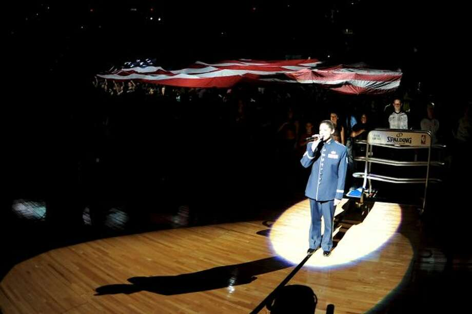 A member of the U.S Air force sings the national Anthem as a giant flag is unfurled in the stands behind her before a NBA basketball game between the Philadelphia 76ers and the San Antonio Spurs at the AT&T Center in San Antonio, Texas on March 25, 2012.