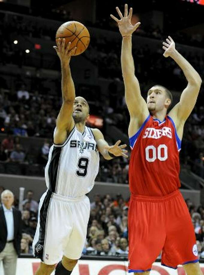 San Antonio Spurs point guard Tony Parker (9) takes a shot as Philadelphia 76ers center Spencer Hawes (00) defends during a NBA basketball game between the Philadelphia 76ers and the San Antonio Spurs at the AT&T Center in San Antonio, Texas on March 25, 2012.