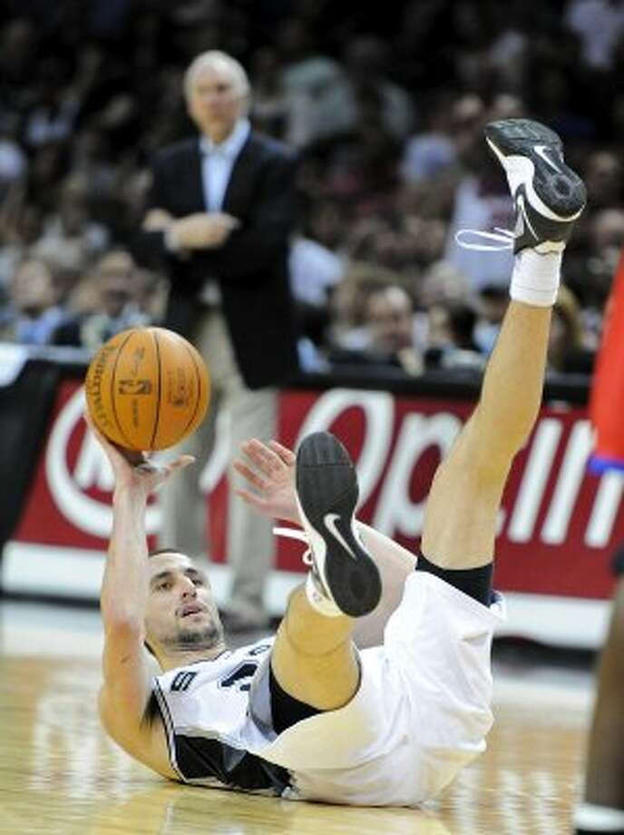 San Antonio Spurs shooting guard Manu Ginobili (20) ends up on the floor with the ball after a hard foul during a NBA basketball game between the Philadelphia 76ers and the San Antonio Spurs at the AT&T Center in San Antonio, Texas on March 25, 2012.