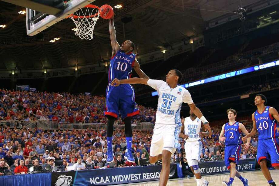 Kansas' Tyshawn Taylor (10) soars past North Carolina's John Henson on a breakaway dunk in the second half. Taylor led the Jayhawks with 22 points. Photo: Dilip Vishwanat / 2012 Getty Images