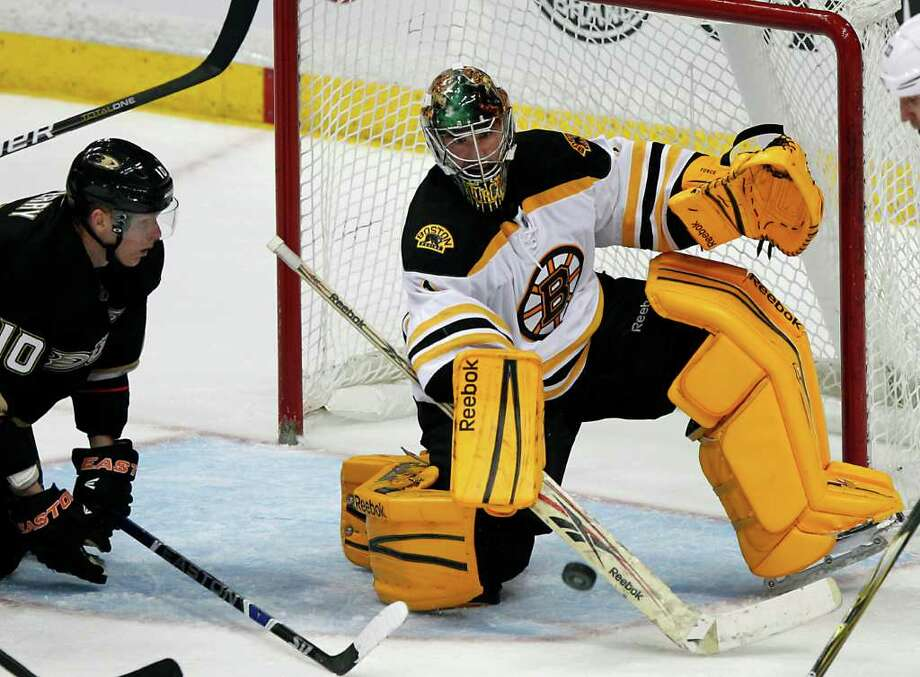 Boston Bruins goalie Marty Turco, right, stops the puck as Anaheim Ducks right wing Corey Perry looks on in the third period of an NHL hockey game in Anaheim, Calif., on Sunday, March 25, 2012. The Bruins won 3-2. (AP Photo/Christine Cotter) Photo: Christine Cotter