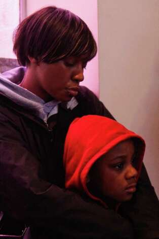 Daina Lee holds her son Amir Brown, 8, during a rally against the shooting death of Florida teenager Trayvon Martin. Amir wears a hoodie in solidarity with the slain teenager who had been wearing a hoodie at the time he was shot by a suspicous neighbor. Photo: JOE DYER / SEATTLEPI.COM