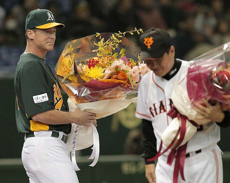 Oakland Athletics' manager Bob Melvin, left, and his counterpart, Yomiuri Giants' Tatsunori Hara are presented bouquets of flowers before their exhibition game at Tokyo Dome, Sunday, March 25, 2012. The Athletics will meet the Seattle Mariners in their two season-opening games of the Major League Baseball in Japan, at Tokyo Dome from Wednesday, March 28. 2012. (AP Photo/Itsuo Inouye) Photo: Itsuo Inouye, Associated Press