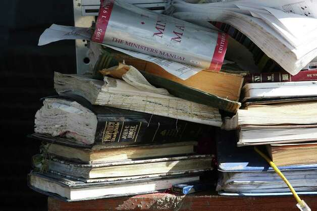 Stacks of books lie on a salvaged pile at Faith Tabernacle Full Gospel Church, Sunday, March 25, 2012. Pastor Darrell Mellene held services outdoors because the church building, located just west of Devine, was destroyed by a tornado last week. Photo: Jerry Lara, San Antonio Express-News / © San Antonio Express-News