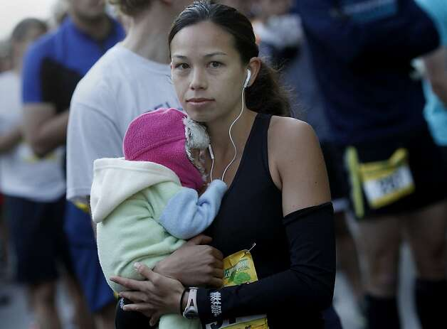 Eventual women's marathon winer Anna Bretan held her six week old daughter Tatum before the start of the marathon. The Oakland Running Festival avoided the rain at the start of the marathon Sunday March 25, 2012. Photo: Brant Ward, The Chronicle