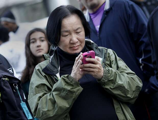 Oakland Mayor Jean Quan checked the weather on her smart phone before the start of the marathon. The Oakland Running Festival avoided the rain at the start of the marathon Sunday March 25, 2012. Photo: Brant Ward, The Chronicle