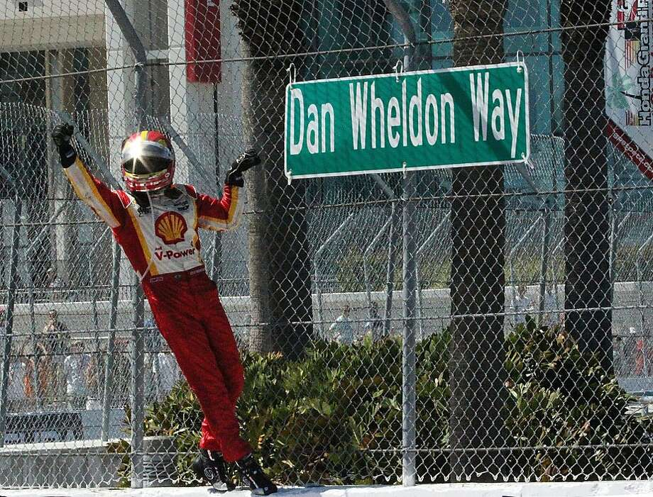 Helio Castroneves, of Brazil, stands next to a sign marking Dan Wheldon Way after Castroneves won the IndyCar Series' Honda Grand Prix auto race in St. Petersburg, Fla., on Sunday, March 25, 2012. Wheldon was killed in a crash in the series' season-ending race last year. (AP Photo/LAT, Richard Coburn) Photo: Richard Coburn, Associated Press