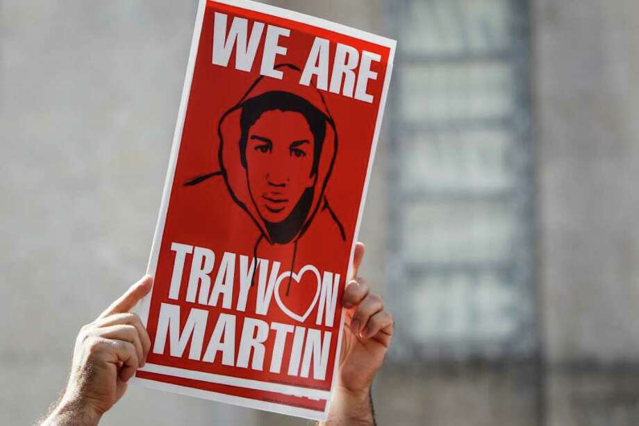 A participants holds a sign in support of justice for the killing of teenager Trayvon Martin in Florida during a Trayvon Martin Movement rally outside of City Hall, Sunday, March 25, 2012, in Houston.   ( Michael Paulsen / Houston Chronicle ) Photo: Michael Paulsen, Staff / © 2012 Houston Chronicle