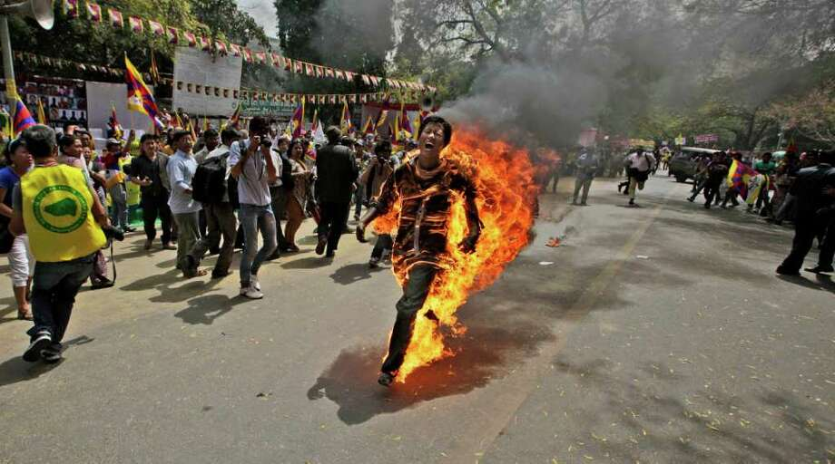A Tibetan exile man, identified as Jampa Yeshi, runs engulfed in flames after self-immolating during a demonstration in New Delhi, India, Monday, March 26, 2012. Yeshi lit himself on fire and ran shouting through a protest in the Indian capital Monday, just ahead of a visit by China's president Hu Jintao and following self-immolations in the Himalayan region against Beijing's rule. (AP Photo/Manish Swarup) Photo: Manish Swarup, Associated Press / AP