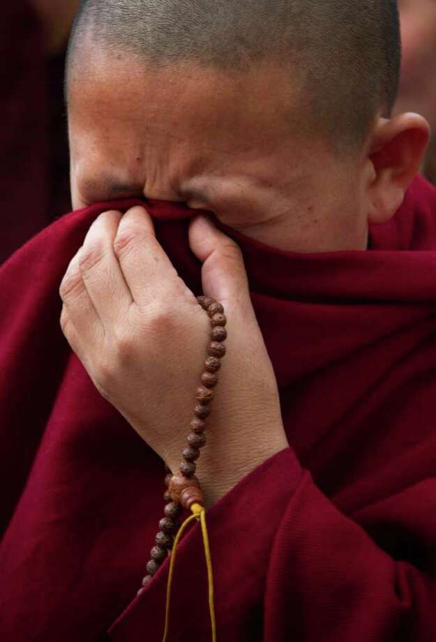 An exile Tibetan Buddhist nun cries in Dharmsala, India, Monday, March 26, 2012 during a candle lit vigil in solidarity with a 27-year-old Tibetan Jamphel Yeshi, who immolated himself in New Delhi, just ahead of a visit by China's president Hu Jintao .(AP Photo/Ashwini Bhatia) Photo: Ashwini Bhatia, Associated Press / AP
