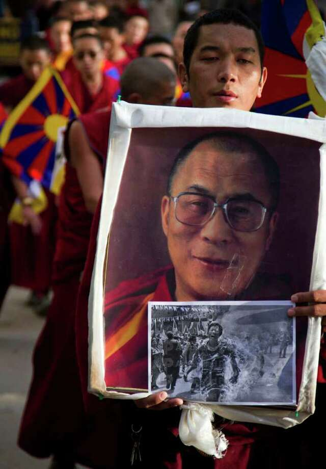 An exile Tibetan Buddhist monk carries a portrait of the Dalai Lama along with a picture of Jamphel Yeshi during a candle lit vigil in Dharmsala, India, Monday, March 26, 2012. Twenty-seven-year-old Tibetan, Jamphel Yeshi, immolated himself Monday in New Delhi just ahead of a visit by China's president Hu Jintao. (AP Photo/Ashwini Bhatia) Photo: Ashwini Bhatia, Associated Press / AP