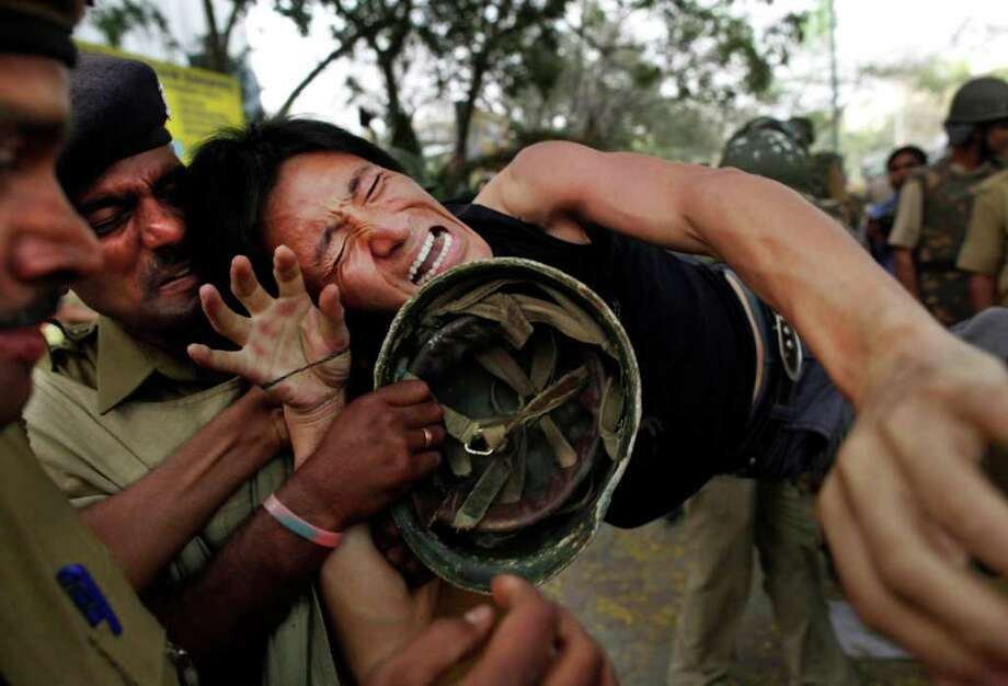 A Tibetan protester is detained by Indian police during a demonstration against China in New Delhi, India, Monday, March 26, 2012. Earlier in the day a Tibetan exile man lit himself on fire and ran shouting through a protest in the Indian capital , just ahead of a visit by China's president Hu Jintao and following self-immolations in the Himalayan region against Beijing's rule. (AP Photo/Kevin Frayer) Photo: Kevin Frayer, Associated Press / AP