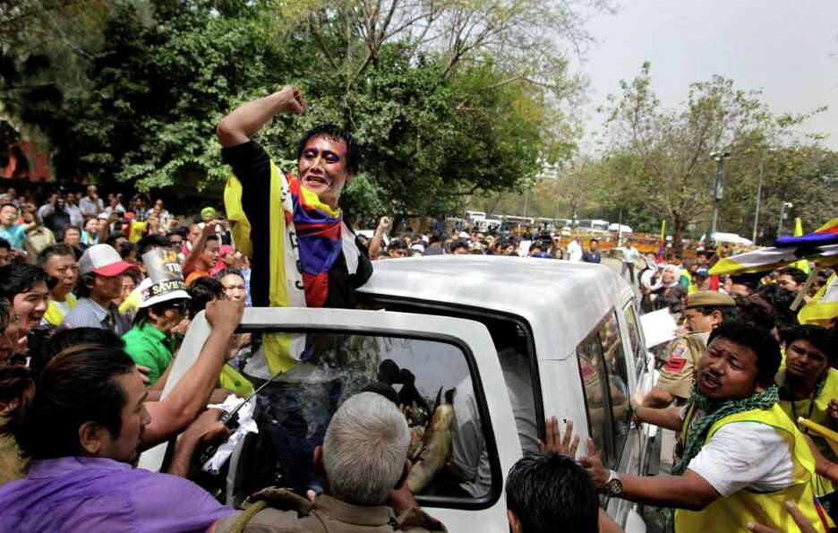 A Tibetan protester chants from the back of a police vehicle carrying a Tibetan exile, identified as