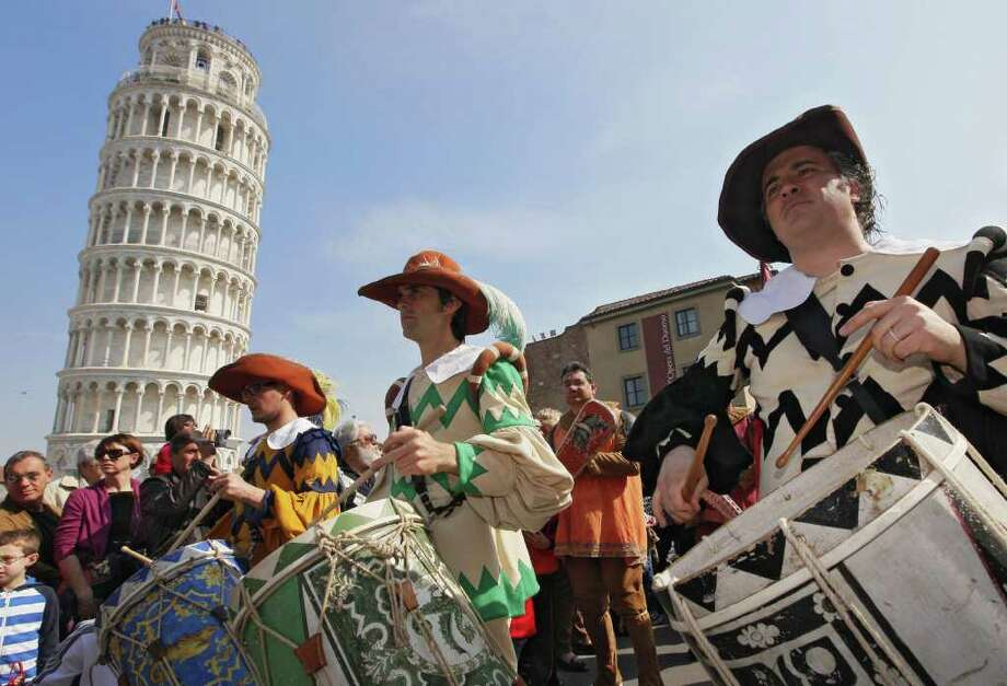 Musicians dressed in medieval costumes parade in front of the Leaning tower of Pisa as they celebrate New Year's day, welcoming in 2013 nine months before the rest of the world on March 25, 2012. The Tuscan city, once a mighty maritime republic which aimed to rival Rome, has revived a tradition dating back centuries, when Pisa had its own calendar which began nine months before Christmas to mark Jesus' miraculous conception.  AFP PHOTO / FABIO MUZZI Photo: FABIO MUZZI, AFP/Getty Images / AFP