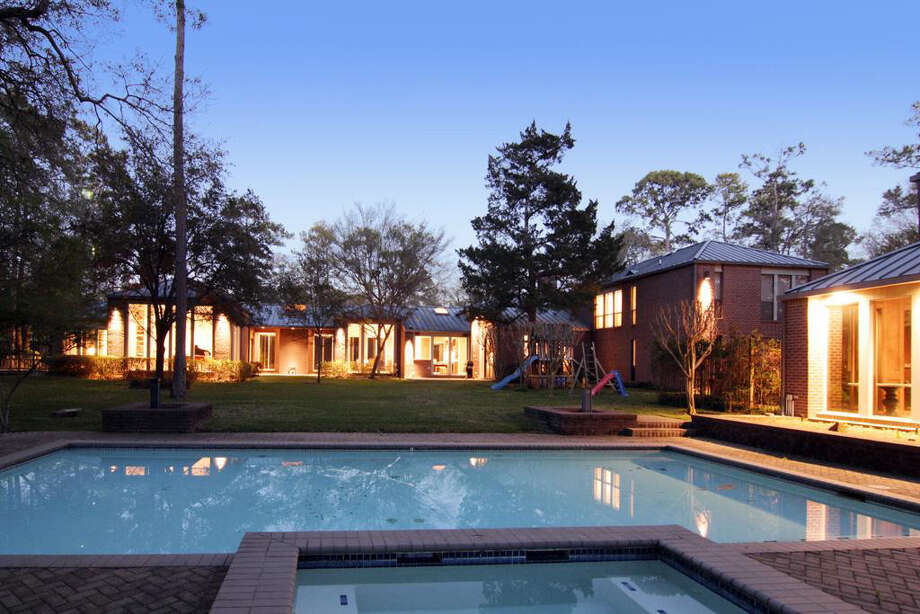 An exterior shot of the back yard of the property, spotlighting the swimming pool and hot tub. Photo: Realtor.com