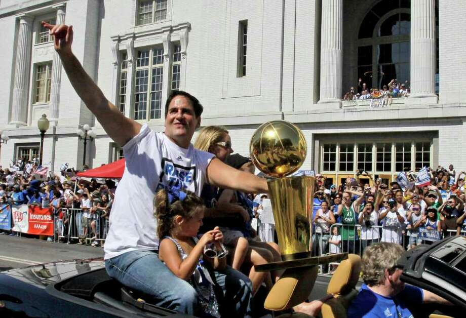 CORRECTS DAUGHTER'S NAME TO ALYSSA, NOT ALEXIS SOFIA - Dallas Mavericks owner Mark Cuban, with his daughter Alyssa, rides with the NBA Championship basketball trophy during the team's victory parade in downtown Dallas, Thursday, June 16, 2011. The Mavericks beat the Miami Heat to win the NBA championship. Photo: AP