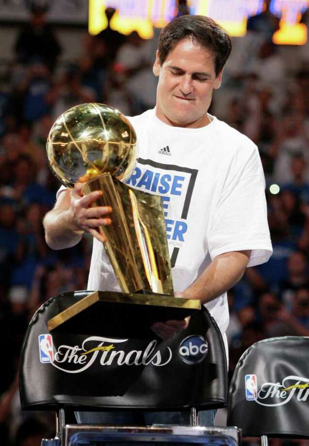 Dallas Mavericks team owner places the Larry O'Brien trophy on a chair at the start of a fan rally at American Airlines Center following the team's NBA Championship title victory parade  Thursday, June 16, 2011, in Dallas. Photo: AP