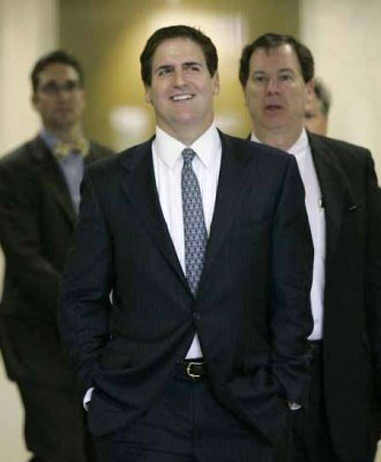 FILE - In this May 26, 2009 file photo, Dallas Mavericks owner Mark Cuban, center, walks out of his federal hearing accompanied by members of his legal team at the Earle Cabell Federal Courthouse in Dallas. A federal judge on Friday, July 17, 2009 dismissed an insider trading lawsuit against Cuban. (AP Photo/Tony Gutierrez, file) (Tony Gutierrez / AP)