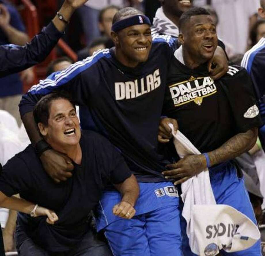 Dallas Mavericks owner Mark Cuban celebrates with Brendan Haywood and DeShawn Stevenson, right, in the final seconds of the second half of Game 6 of the NBA Finals basketball game against the Miami Heat Sunday, June 12, 2011, in Miami. The Mavericks won 105-95 to win the series. (AP Photo/David J. Phillip) (David J. Phillip / AP)