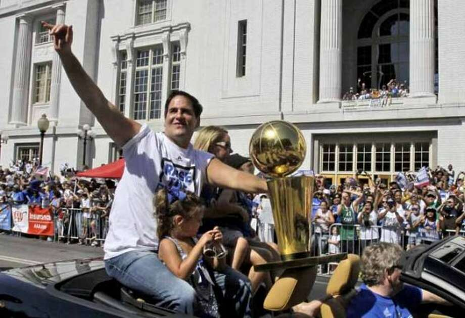 CORRECTS DAUGHTER'S NAME TO ALYSSA, NOT ALEXIS SOFIA - Dallas Mavericks owner Mark Cuban, with his daughter Alyssa, rides with the NBA Championship basketball trophy during the team's victory parade in downtown Dallas, Thursday, June 16, 2011. The Mavericks beat the Miami Heat to win the NBA championship.  (AP Photo/LM Otero) (LM Otero / AP)