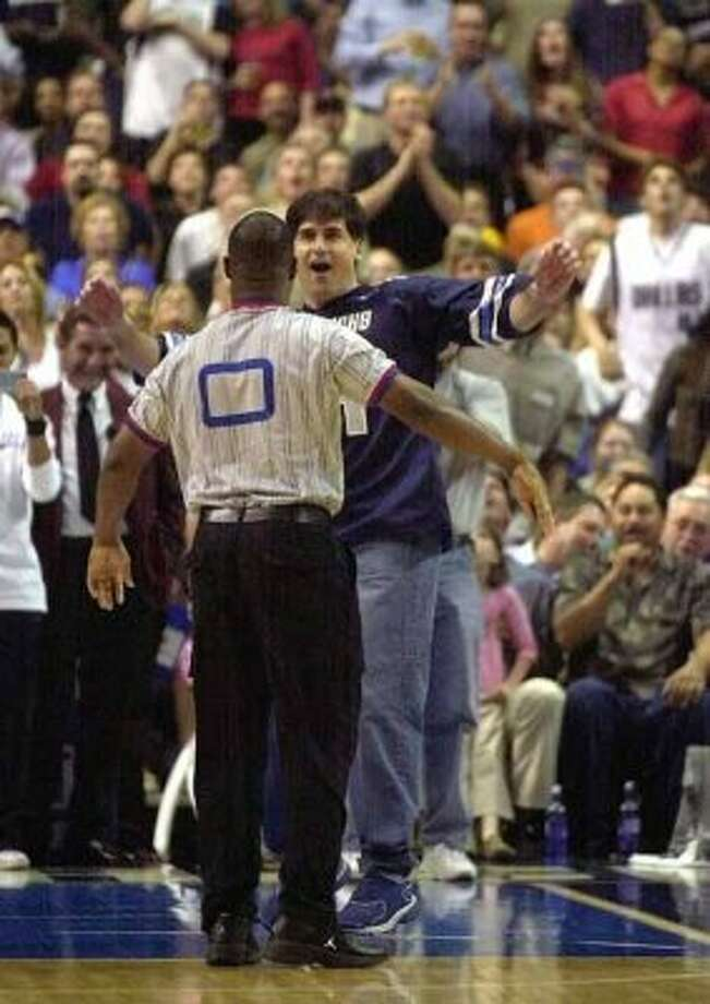 Dallas Mavericks owner Mark Cuban, rear, jumps back as a actor posed as a referee shoves him backwards during the first half of the Mavericks, New Orleans Hornets game, Tuesday Apri. 1, 2003, in Dallas. Cuban continued to get into a scuffle with the actor as fans reacted in what turned out to be an April Fool's Day joke. (AP Photo/Tony Gutierrez) (TONY GUTIERREZ / AP)