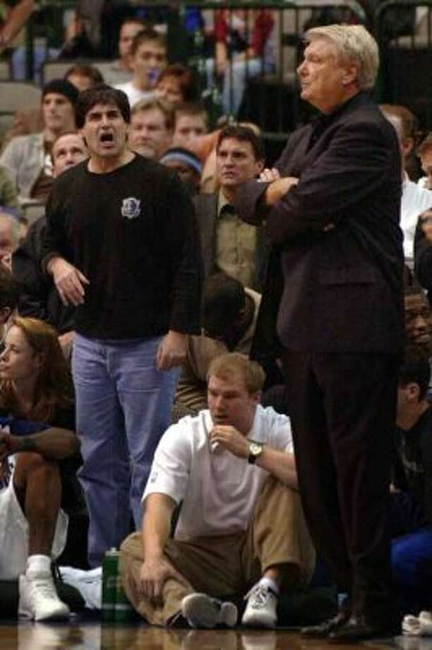 Dallas Mavericks owner Mark Cuban, left, standing, complains to the referees, saying a Philadelphia 76ers player should have been called for a foul, as coach Don Nelson, right, stands nearby during the Mavericks' 125-122 double-overtime win over the Philadelphia 76ers, Wednesday, Jan. 14, 2004, in Dallas. A few hours after Cuban tried to diffuse speculation about Nelson's job security by telling Nelson he would remain coach and general manager, the Mavericks played one of their most exciting games of the season. (AP Photo/Tony Gutierrez) (*HFI*, AP)