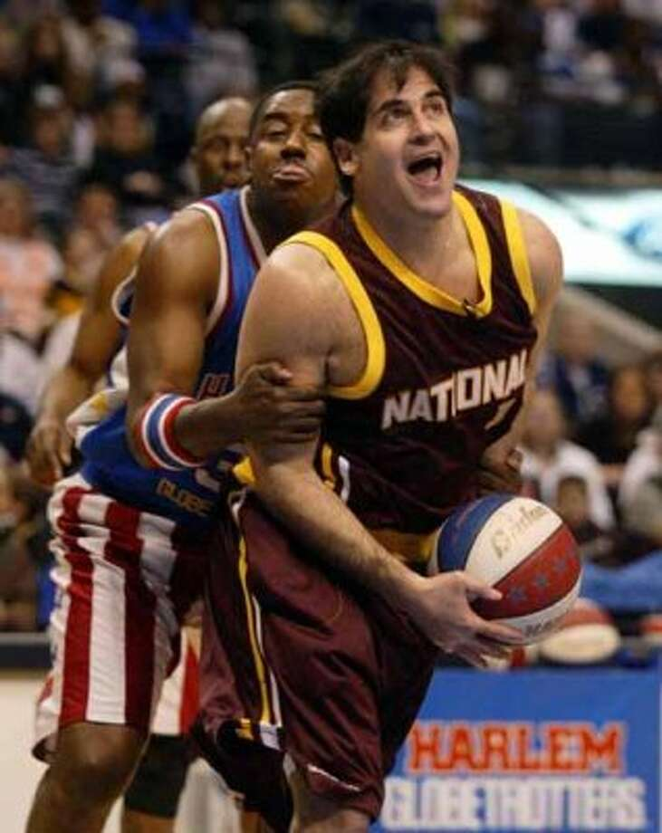 Harlem Globetrotters' Paul Gaffney, left, fouls New York Nationals guest player and Dallas Mavericks owner Mark Cuban, right, during a game in Dallas on Saturday, Feb. 7, 2004. (AP Photo/The Dallas Morning News, Michael Ainsworth) (AP)