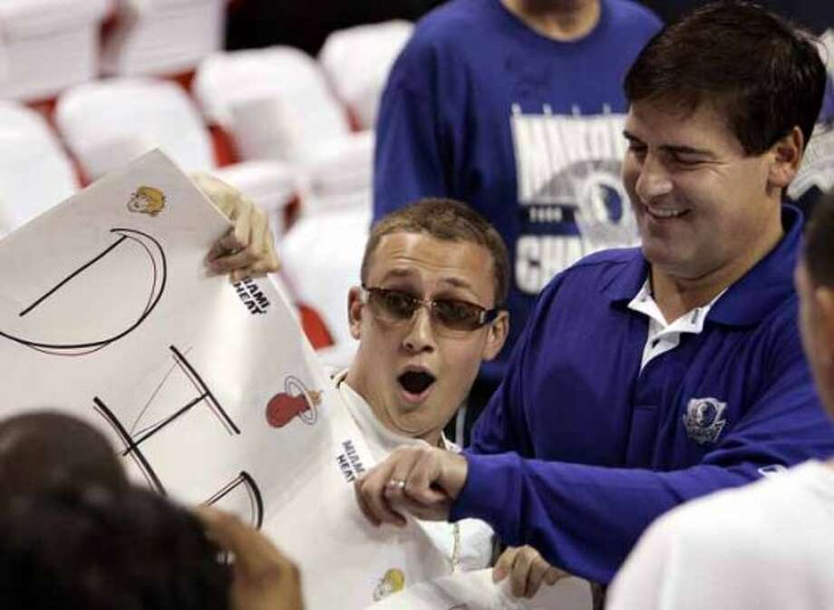 Dallas Mavericks owner Mark Cuban, right, tries to take the sign of Miami Heat fan Eric Topchik prior to the start of Game 5 of the NBA Finals basketball game between the Mavericks and the Heat at the American Airlines Arena in Miami on Sunday, June 18, 2006. (AP Photo/J. Pat Carter) (AP)
