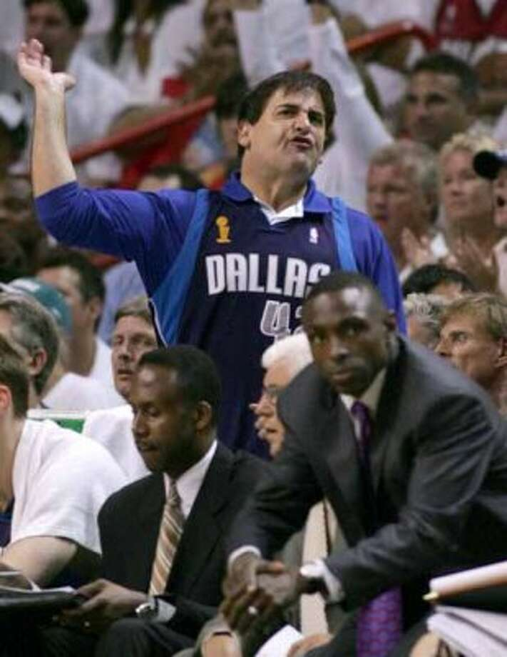 Dallas Mavericks owner Mark Cuban (C, standing) reacts as a foul is called on his team as they faced the Miami Heat in the first half during Game 5 of their NBA Finals basketball game in Miami June 18, 2006. Below right is Mavericks head coach Avery Johnson. REUTERS/Marc Serota     (UNITED STATES) (REUTERS)