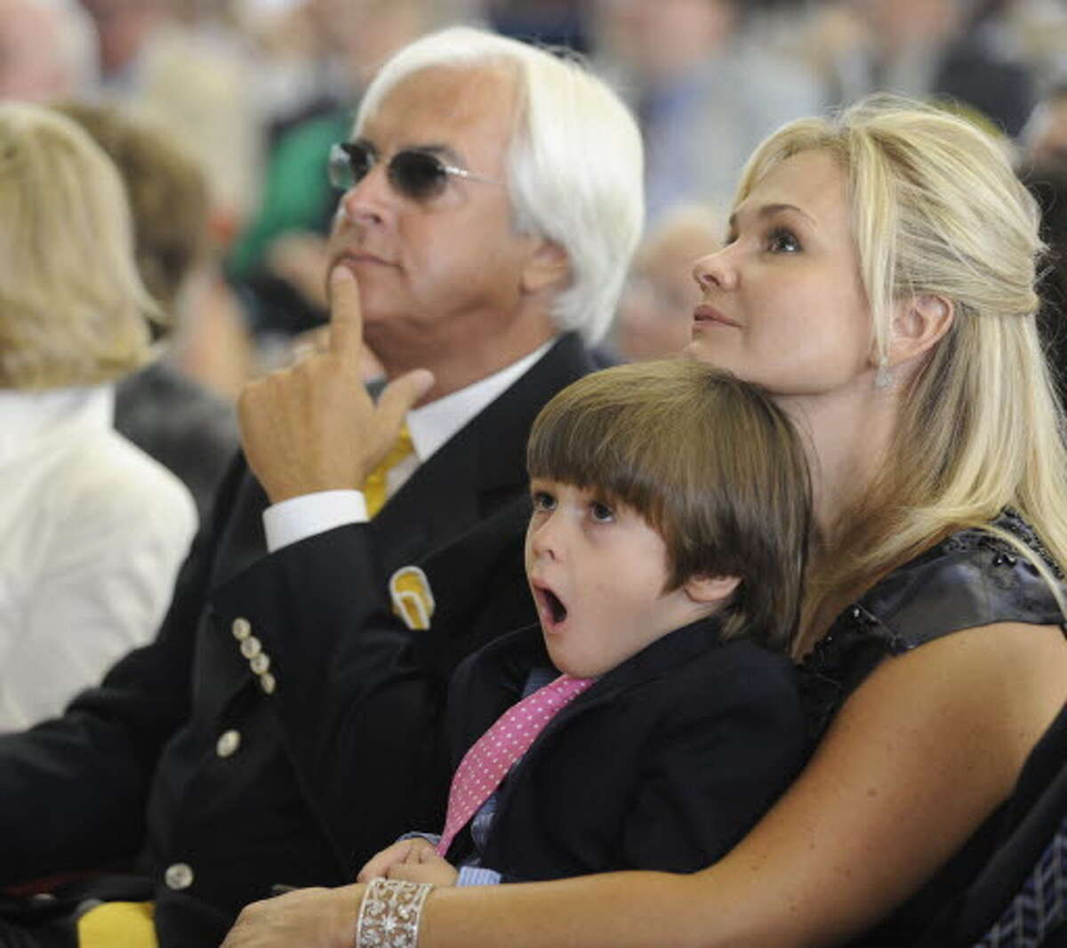 Trainer Bob Baffert(l) listens intently to the speeches of inductees while his son Bode yawns on his mother Jill's lap before his dad's turn to be inducted in to the Thoroughbred Racing Hall of Fame at the ceremony held at the Fasig Tipton sales pavilion in Saratoga Springs, New York August 14, 2009. (Skip Dickstein / Times Union)