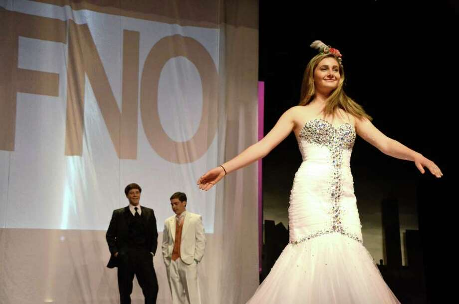 Kate Gilhool was the first model to dazzle the runway on Saturday night, March 24, 2012, at New Canaan High School's Fashion Night Out.  She was an MC along with Chris Green and Doug Reilly, in back, who were on deck for their own walk for the 10th Annual Prom Fashion Show. Photo: Jeanna Petersen Shepard
