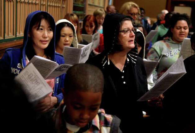 Congregants participate in a service at Middle Collegiate Church in New York, Sunday, March 25, 2012. Church-goers were invited to wear hoodies to services to show their support for justice in the case of Trayvon Martin, an unarmed black teenager who was wearing a hoodie on the night he was killed by a neighborhood watch captain in Florida.  (AP Photo/Seth Wenig) Photo: Seth Wenig