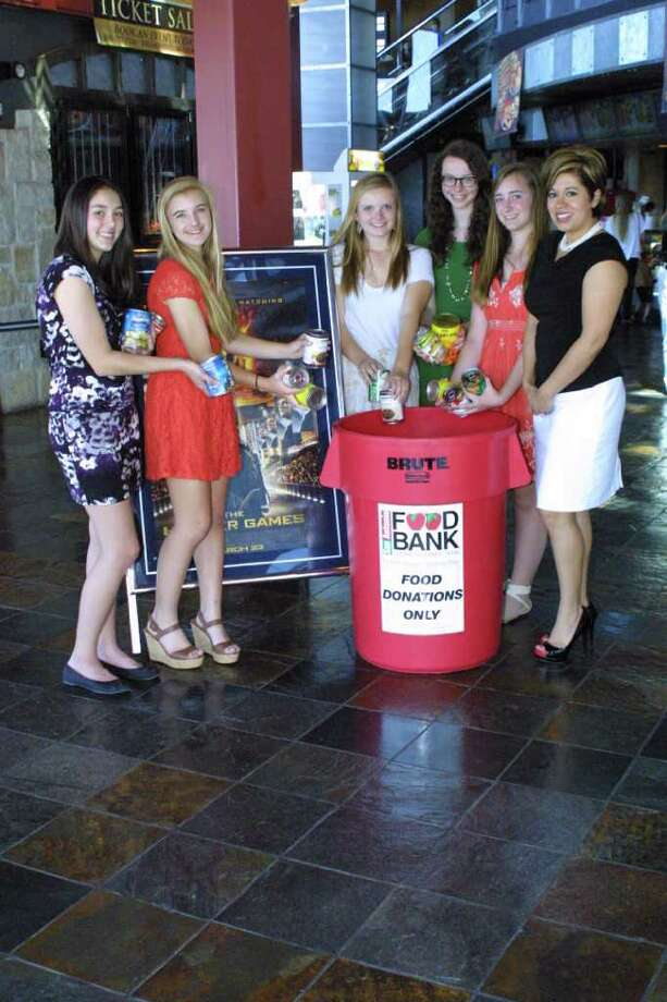 """The Alamo Heights High School Destination ImagiNation team makes their donations to the San Antonio Food Bank prior to the start of """"The Hunger Games"""" movie late March 22. Pictured are team members (from left) Caspin Jones, Ellery Vaughan, Cally Decherd, Annie Daubert, Lauren Hampton, and Erica Benavides, community investments director for the San Antonio Food Bank. Photo: Courtesy Photo"""
