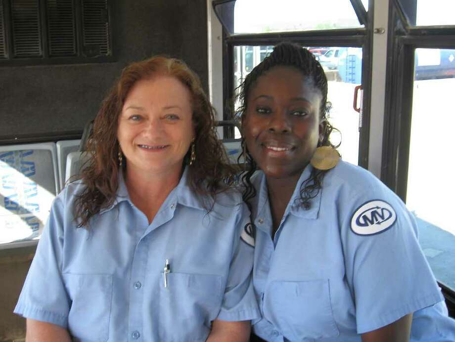 Leanne Guller, left, and Regina Lemons, sit in a bus they usually would be driving filled with construction workers going to the Motiva Port Arthur refinery crude expansion project from a parking area on Texas 73 in Port Arthur. They have been driving for MV Transportation Inc. for almost four years, but the job is coming to an end as the refinery expansion nears completion. They've been happy with the work and have prospects beyond the coming layoffs. Dan Wallach/The Enterprise