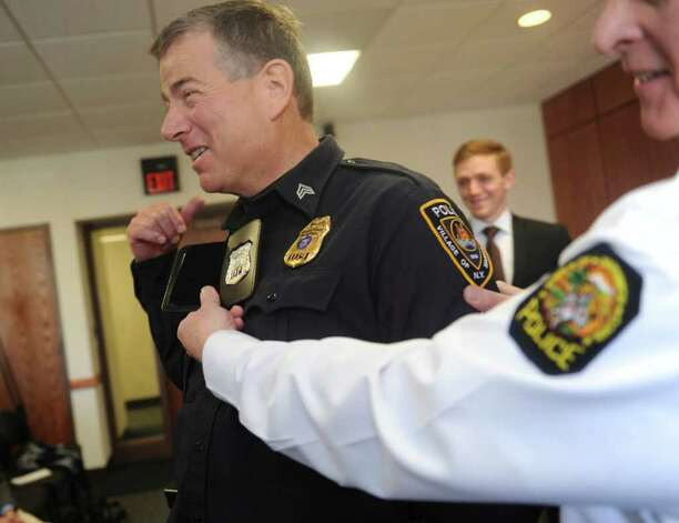 Police Chief James Heavey noticed that new officer Luke Kelly's badge is   110, one number after his father, Sgt. Regan Kelly of Mamaroneck, N.Y., whose badge number was 109.  Heavey changed the badge for Luke so both will have badge 109.  Four new members of the Greenwich Police Department were sworn in Monday, March 26, 2012, at Town Hall. Photo: Helen Neafsey / Greenwich Time