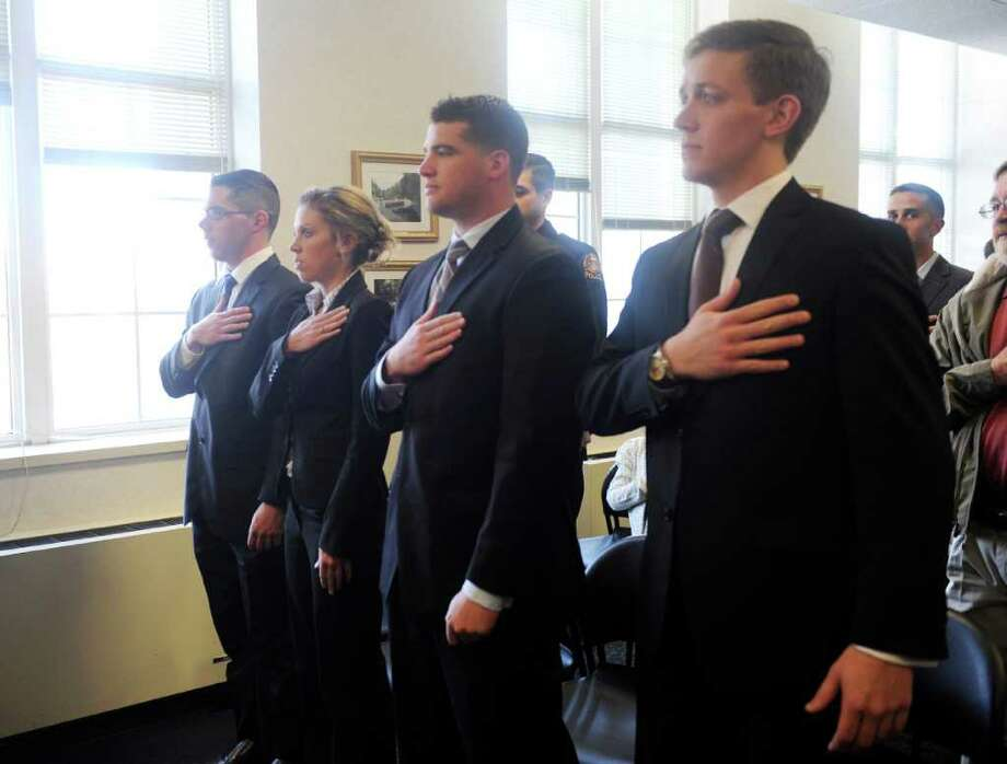 From left, Christopher M. Wallace, Aran J. Tradel, Alan C. Pesce and Luke A. Kelly say the pledge of alliegence during a swearing in ceremony for police Greeenwich officers in Town Hall Monday, March 26, 2012.  . Photo: Helen Neafsey / Greenwich Time