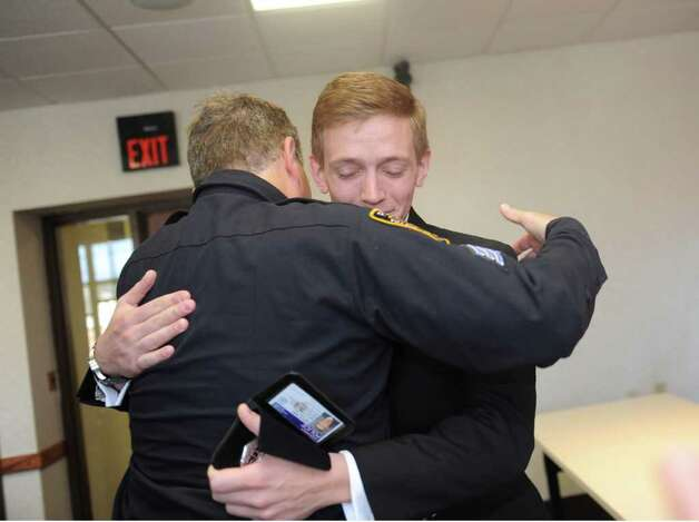 Sgt. Regan Kelly, Mamaroneck, N.Y. police officer, hugs his son, Luke during his swearing in as a Greenwich officer in Town Hall Monday, March 26, 2012. Photo: Helen Neafsey / Greenwich Time