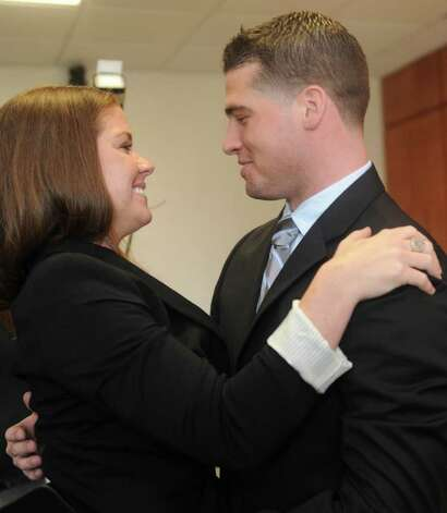 Alan C. Pesce hugs his wife, Shannon, after she gave him his badge during his swearing in as a Greenwich officer at Town Hall Monday, March 26, 2012. Photo: Helen Neafsey / Greenwich Time