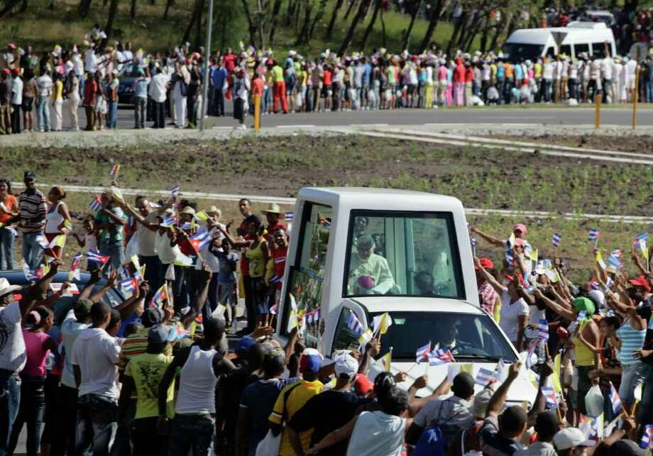 Pope Benedict XVI waves from the popemobile as is being driven after his arrival in Santiago de Cuba Monday March 26, 2012. Photo: AP