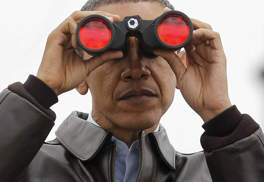 President Barack Obama looks through binoculars to see North Korea from Observation Post Ouellette in the Demilitarized Zone, the tense military border between the two Koreas, in Panmunjom, South Korea, Sunday, March 25, 2012. (AP Photo/Pablo Martinez Monsivais) Photo: Pablo Martinez Monsivais, Associated Press