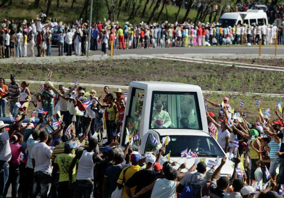 Pope Benedict XVI waves from the popemobile as is being driven after his arrival in Santiago de Cuba Monday March 26, 2012.(AP Photo/Desmond Boylan,Pool)
