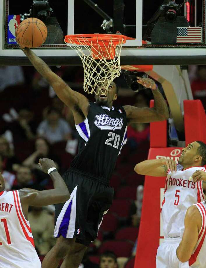 Sacramento Kings small forward Donte Greene (20) dunks the ball over Houston Rockets center Samuel Dalembert (21) and shooting guard Courtney Lee (5) during the first half of a basketball game at the Toyota Center Monday, March 26, 2012, in Houston. Photo: Cody Duty, Houston Chronicle / © 2011 Houston Chronicle