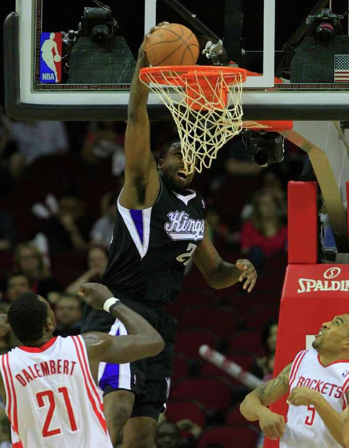 Sacramento Kings small forward Donte Greene dunks the ball over Houston Rockets center Samuel Dalembert, left, and shooting guard Courtney Lee, right, during the first half of a basketball game at the Toyota Center Monday, March 26, 2012, in Houston. Photo: Cody Duty, Houston Chronicle / © 2011 Houston Chronicle