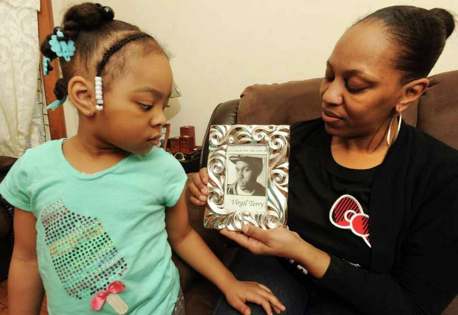Bonita Garcia holds a framed photograph of her son Virgil Terry on March 13, 2012 in Schenectady, N.Y. Terry's daughter Jazmarie Terry, age 5, looks at her father's photograph. Terry was gunned down on a city street. (Lori Van Buren / Times Union) Photo: Lori Van Buren