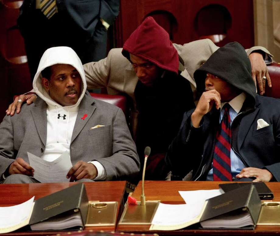 Sen. Kevin Parker, D-Brooklyn, left, Sen. Bill Perkins, D-New York, center, and Sen. Eric Adams, D-Brooklyn, wear hooded sweatshirts during session in the Senate Chamber in Albany, N.Y., on Monday, March 26, 2012. The senators wore the sweatshirts to protest the shooting death of Florida teen Trayvon Martin by a neighborhood watch volunteer. (AP Photo/Mike Groll) Photo: Mike Groll